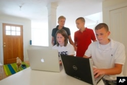 Kel Kelly, back left, and her children Julia McGovern, 18, front left, Shaun McGovern, 16, right, and Patrick McGovern, 14, gather around their computers at their vacation home in Wellfleet, Mass.
