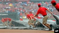 Members of the St. Louis Cardinals grounds crew pull the tarp over the infield as it rains during the first inning of a baseball game against the Minnesota Twins, in St. Louis, June 16, 2015.