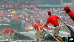 Members of the grounds crew -- the people who take care of a sports field -- pull the tarp over the infield as it rains during a baseball game in St. Louis. (AP Photo/Scott Kane)