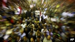 In this zoom effect photo taken with a slow shutter speed, supporters of Egypt's ousted President Mohammed Morsi gather during a demonstration in front of Cairo University, where protesters have installed their camp in Giza, southwest of Cairo, Egypt, Jul