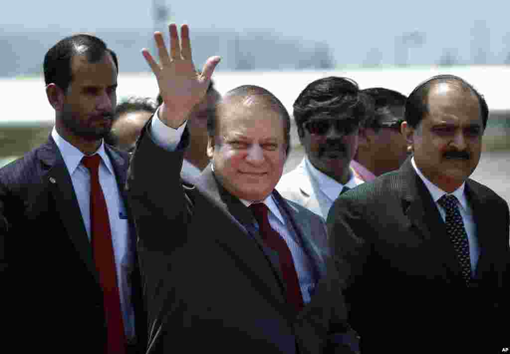 Pakistani Prime Minister Nawaz Sharif waves as he arrives to attend the swearing in ceremony of India's prime minister elect Narendra Modi in New Delhi, May 26, 2014.