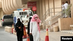 Seorang pria memakai masker untuk menghindari penularan coronavirus, berjalan dekat rumah sakit di Khobar, Dammam, Arab Saudi (21/5).