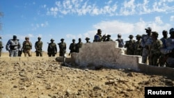 Malian and French soldiers stand next to a mass grave in Aguelhok, Mali, January 24, 2014.