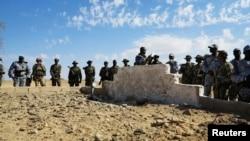 Tentara Mali dan Tentara Prancis berdiri di dekat kuburan masal di Aguelhok, Mali, 4/1/ 2014.