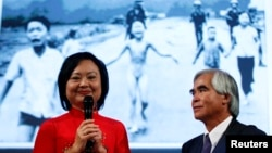 Photojournalist Nick Ut and Kim Phuc (L) attend the presentation of the latest Leica equipment at Photokina 2012, the world's largest fair for imaging, in Cologne, Germany, Sep. 17, 2012. Ut took the iconic 1972 Vietnam War photograph of Kim Phuc running naked down a road after being burned in a napalm attack near Trang Bang.