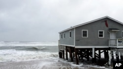 Waves wash ashore hitting a house as winds and storm surge from Tropical Storm Maria lash North Carolinas Outer Banks as the storm moves by well off-shore on Wednesday, Sept. 27, 2017. Dare County officials said the high tide flooded some roads in the area and travel is hazardous.