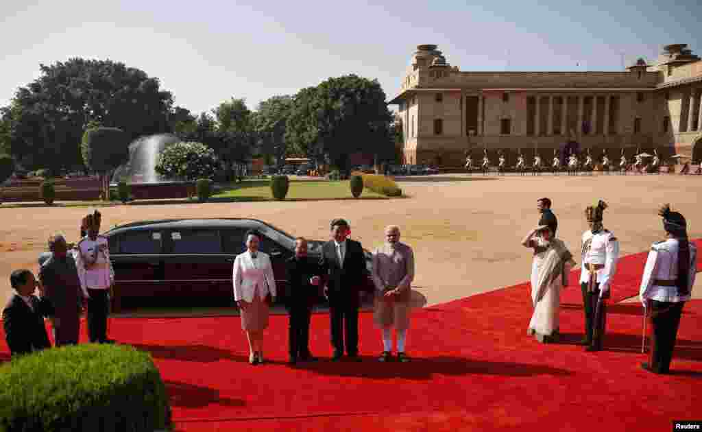 Chinese President Xi Jinping (center, 2nd right) shakes hands with his Indian counterpart Pranab Mukherjee (2nd left) as Xi's wife Peng Liyuan (center left) and India's Prime Minister Narendra Modi (center right) look on during Xi's ceremonial reception at the forecourt of India's Rashtrapati Bhavan presidential palace, New Delhi, Sept. 18, 2014.