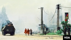 FILE - Photo shows Cambodian Buddhist monks (C) walking near a tank along a street in Phnom Penh, July 7, 1997.