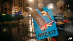Vehicles drive past an anti-Brexit sign that is placed near the Parliament in London, Jan. 29, 2019.