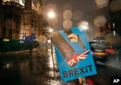 FILE - Vehicles drive past an anti-Brexit placard that is placed near the Parliament in London, Jan. 29, 2019.