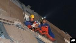 Seorang petugas penyelamat membawa seorang bayi dari gedung yang rusak akibat gempa di Tainan, Taiwan, Sabtu (6/2).