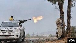 Pasukan NTC Libya dengan senjata mesin menembaki pasukan pro-Gaddafi di kota Sirte (7/10).