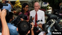 Alan Morison (R), an Australian, and Thai national Chutima Sidasathian, reporters for the Phuketwan news website, speak to media as they arrive to a criminal court in Phuket, April 17, 2014.