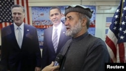 Afghan journalist Abdul hai Warshan talks during an interview in front of cardboard cut-outs of U.S. President Barack Obama and Republican presidential candidate Mitt Romney at the U.S. embassy in Kabul, November 7, 2012.