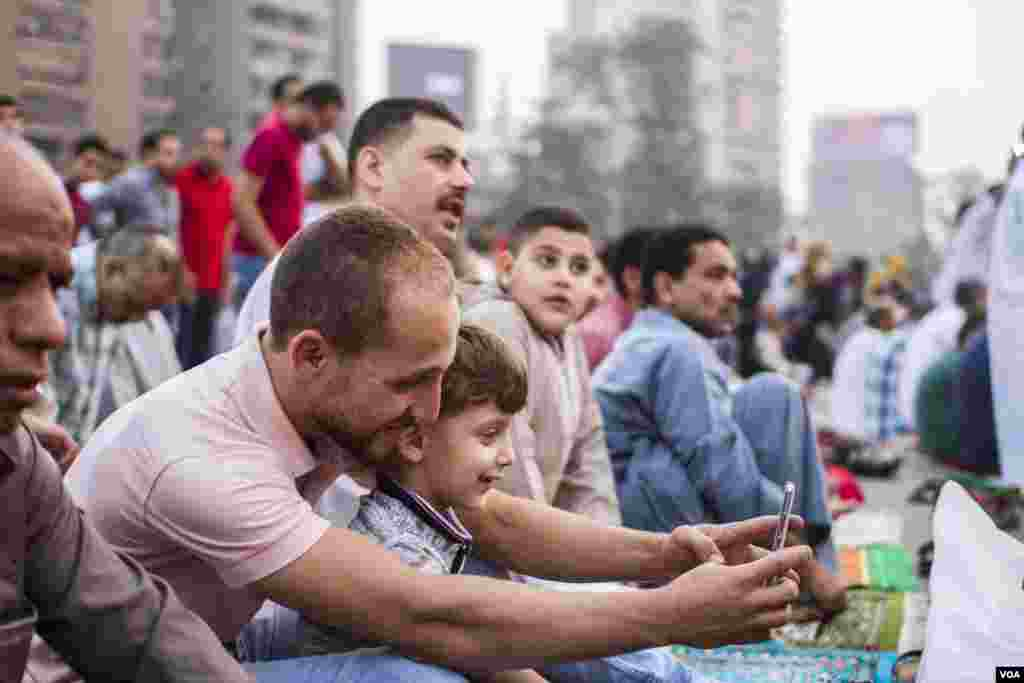 Assem a 32 old father taking a selfie with his son Omar 6 years young during Eid Al-Fitr prayers at Mostafa Mahmoud square in Cairo, Egypt, June 25, 2017. (H. Elrasam/VOA)