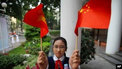 Tư liệu: Một nữ sinh vẫy cờ VN (trái) và cờ TQ (phải) vào dịp Chủ tịch TQ Tập Cận Bình sang thăm VN, ảnh chụp tại Hà Nội ngày 22/12/2011. (AP Photo/Na Son Nguyen, Pool)