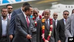 Umushikiranganji ajejwe imigenderanire wa Eritreya, Osman Sale, hagati i buryo kw'ifoto, yakiwe n'umushikiranganji wa mbere wa Etiyopiya, Abiy Ahmed, i bubamfu kw'ifoto, ku kibuga c'indege co ku murwa mukuru, Addis Abeba