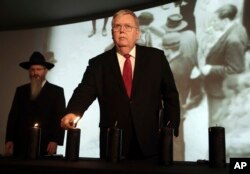 FILE - U.S. Ambassador to Russia John Tefft lights a candle at a ceremony marking the International Holocaust Remembrance Day in the Jewish Museum and Tolerance Center in Moscow, Russia, Jan. 27, 2017. At left is Russia's chief rabbi, Berel Lazar.