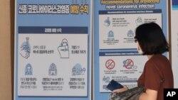 在首爾景福宮,戴著口罩的行人走在預防冠狀病毒預防措施的橫幅前。 (2020年8月16日)