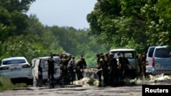 Para tentara Ukraina membersihkan daerah tempat pemberontak pro-Rusia membunuh tentara Ukraina di kota Volnovakha, Donetsk (22/5).