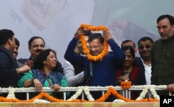 """Incumbent Delhi Chief Minister Arvind Kejriwal, center, is garlanded at Aam Aadmi Party, or """"common man's"""" party headquarters as they celebrate the party's victory in New Delhi, India, Feb. 11, 2020."""
