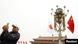 A man uses his mobile phone under Chinese and Japanese flags in front of the Tiananmen Gate ahead of Japan's Prime Minister Shinzo Abe's visit, in Beijing, Oct. 25, 2018.