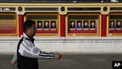 A man walks past portrait of communist party members on display outside Imperial Ancestral Temple in Beijing, China, November 12, 2012.
