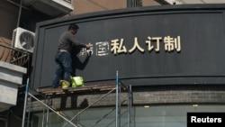 """上海一名工人移走商店招牌上的""""韩国""""两字(2017年3月15日照片)"""
