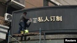Một công nhân đang tháo các ký tự tiếng Hoa của chữ 'Nam Hàn' trên bảng hiệu của một cửa hàng ở Thượng Hải, Trung Quốc, ngày 15/3/2017
