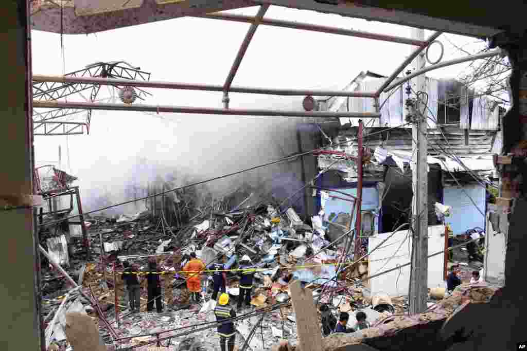 Thai firefighters fight the blaze after an explosion at a scrap shop in Bangkok, Thailand, April 2, 2014. Workers at the scrap shop in Thailand's capital on Wednesday accidentally detonated a large bomb believed to have been dropped during World War II, k
