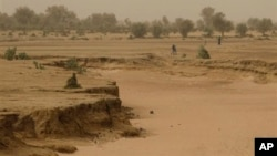 In this April 30, 2012 photo, people walk past a dry seasonal riverbed in the Matam region of northeastern Senegal. Since late 2011, aid groups had warned that devastating drought again weakened communities where children already live perilously close to