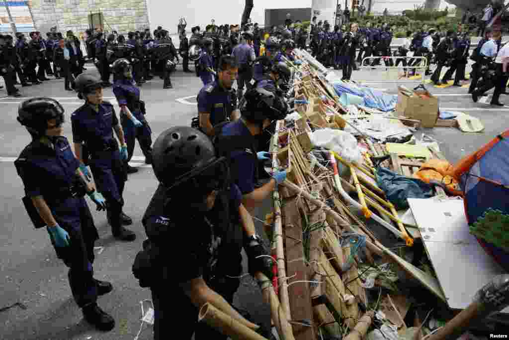 A polícia derruba uma barricada montada pelo movimento pró-democracia à porta da sede do Governo em Hong Kong, Dez. 11, 2014.