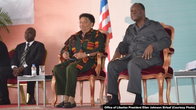 From left, Liberian Defense Minister Brownie Samukai, Liberian President Ellen Johnson Sirleaf and Ivory Coast President Alassane Ouattara attend the Joint Council of Chiefs and Elders Meeting in Guigloe, Ivory Coast, Jan. 18, 2016.