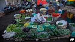 A roadside vendor arranges vegetables at his shop early in the morning in Ahmadabad, India, Dec. 29, 2015.