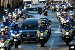 FILE - A motorcycle parade follows the hearse carrying the casket of French rock star Johnny Hallyday, down the Champs-Elysees avenue in Paris, Saturday, Dec. 9, 2017.