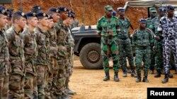Les soldats français se tiennant près des soldats ivoiriens à Toumodi, lors d'une formation militaire avant le départ des militaires ivoiriens pour le Mali, le 6 avril 2013.
