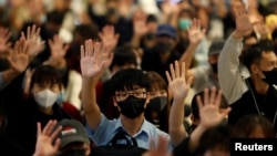 Protesters wearing face masks hold up their hands during an anti-government protest at Yoho Mall in Yuen Long, Hong Kong, China, Nov. 21, 2019.
