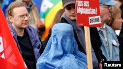 FILE - A protester dressed in traditional burqa garment attends a demonstration against the deployment of German armed forces in Afghanistan in front of the Brandenburg Gate in Berlin.