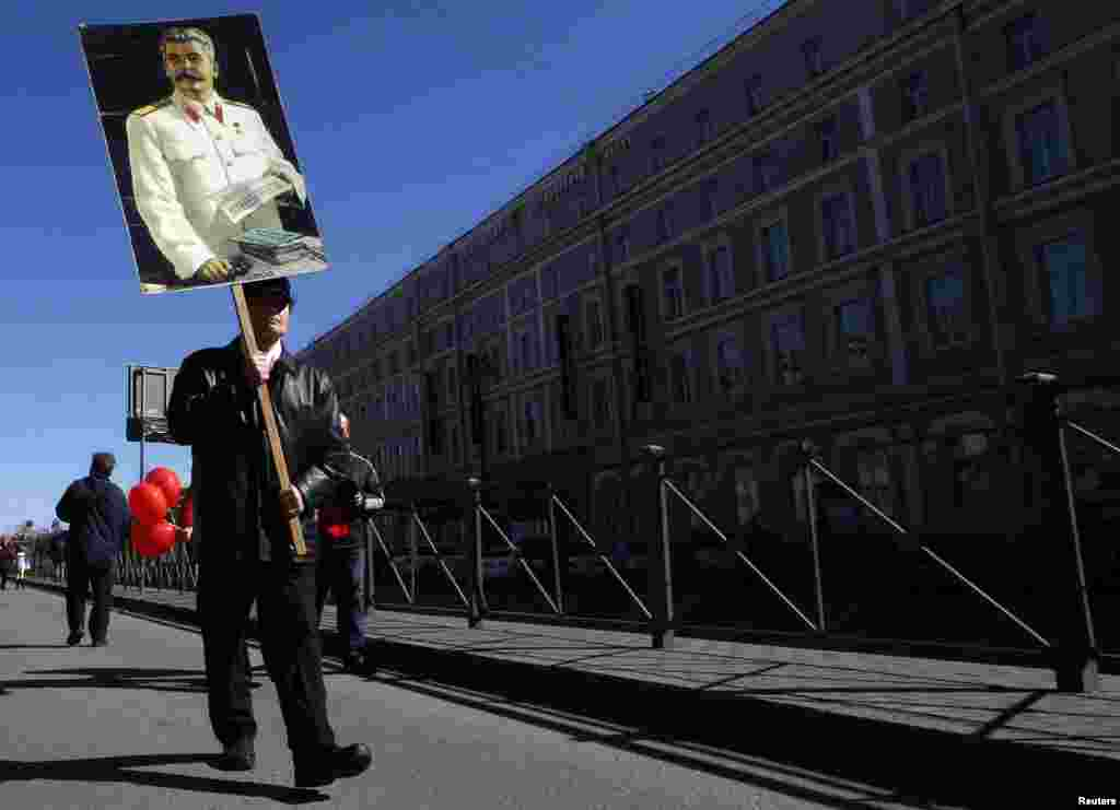 A man carries a portrait of Soviet dictator Joseph Stalin during a Labor Day, or May Day, march in St. Petersburg, Russia, May 1, 2013.