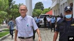 Seorang polisi mengawal Richard Daschbach (kiri), mantan misionaris Pennsylvania, menuju ruang sidang di pengadilan Oecusse, Timor Leste, 23 Februari 2021. (AP Photo / Raimundos Oki)
