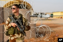 FILE - A French airman stands guard near a Hartford drone, at the Niamey military base, in Niger.