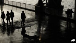 A patrolling police officer, center, is silhouetted under a bridge on the South Bank by the River Thames as he looks over at an embracing couple after a rain shower in London, 7 Jan 2011