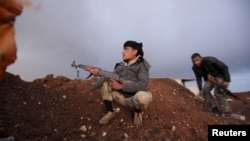 Rebel fighters of the Al-Furqan brigade sit on a look-out point with their weapons in Aziziyah village, southern Aleppo countryside, Syria, March 5, 2016.
