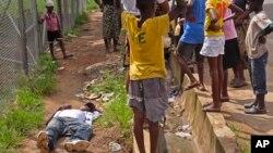 Deca okupljena oko čoveka koji je pao na ulici, a za koga se sumnja da je inficiran virusom ebole, Liberija, 19. avgust 2014.