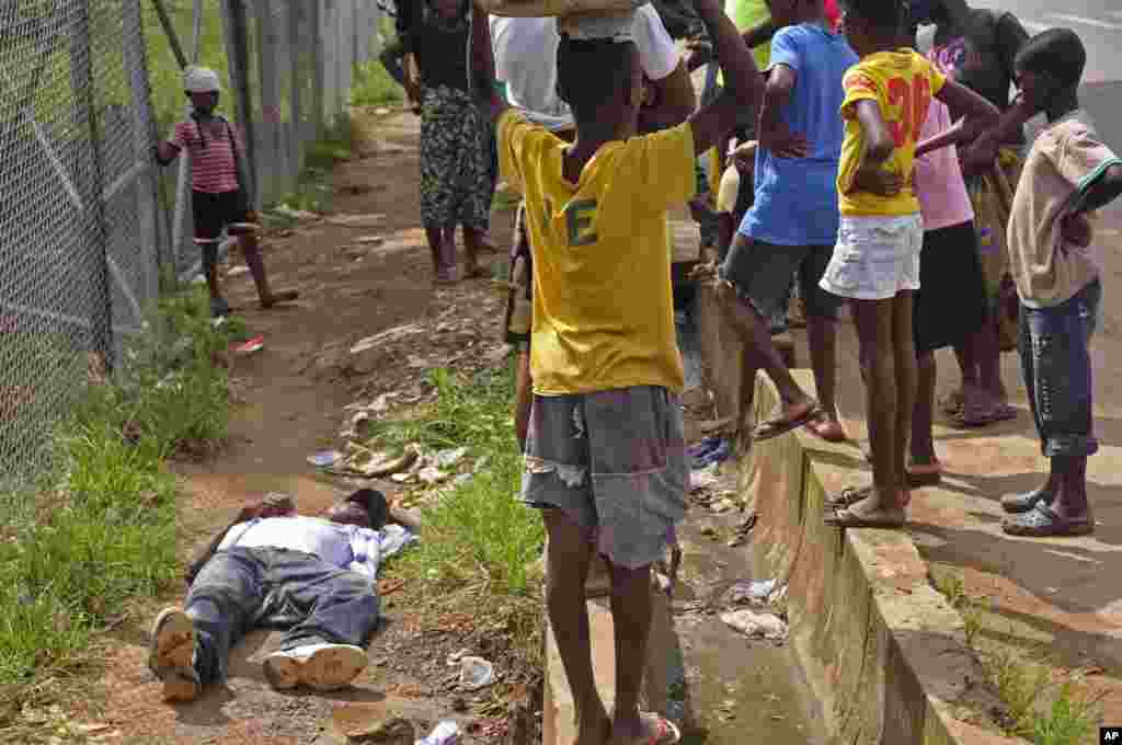 Children surround a man suspected of having contracted the Ebola virus,Monrovia, Liberia, Aug. 19, 2014.
