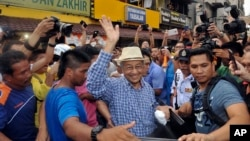 Mantan PM Malaysia, Mahathir Mohamad (bertopi) ikut hadir pada acara unjuk rasa menuntut pengunduran diri PM Najib Razak di Kuala Lumpur, Minggu (30/8).