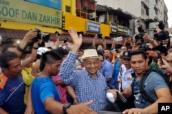 Malaysia former Prime Minister Mahathir Mohamad, center, waves to activists from the Coalition for Clean and Fair Elections (BERSIH) on his arrival during a rally in Kuala Lumpur, Malaysia, Aug. 30, 2015.