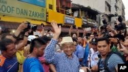 Mantan Perdana Menteri Malaysia Mahathir Mohamad, tengah, melambaikan tangan ke arah aktivis dari Coalition for Clean and Fair Elections (BERSIH) ketika tiba di demo di Kuala Lumpur, Malaysia, 30 Agustus 2015.