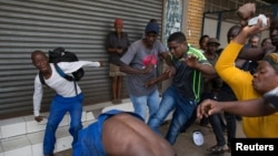 A vigilante mob attacks a Nigerian migrant outside a church in Pretoria, South Africa, Feb. 18, 2017.