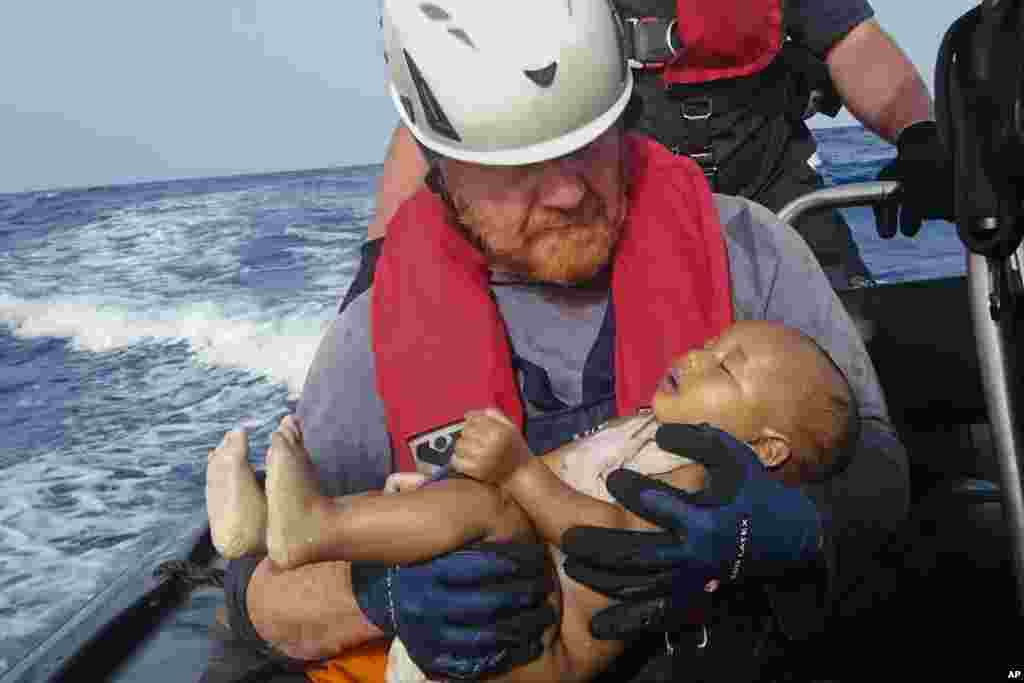A Sea-Watch humanitarian organization crew member holds a drowned migrant baby, during a rescue operation off the coasts of Libya. Survivor accounts have pushed to more than 700 the number of migrants feared dead in Mediterranean Sea shipwrecks over three days in the past week.